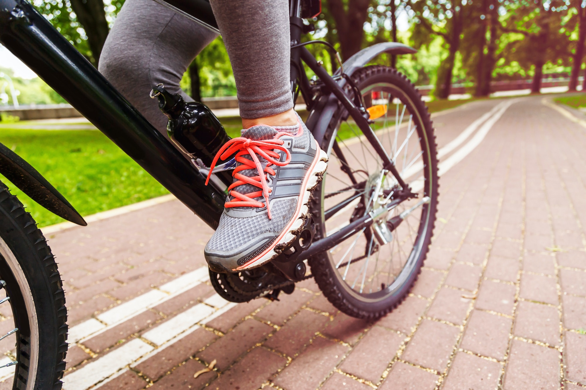 Close-up image of cyclist man feet riding mountain bike on trail in summer